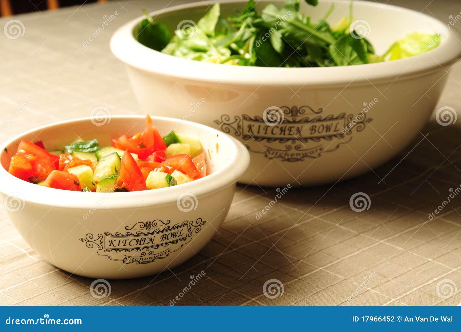 Twee keukenkommen die met verse salade worden gevuld