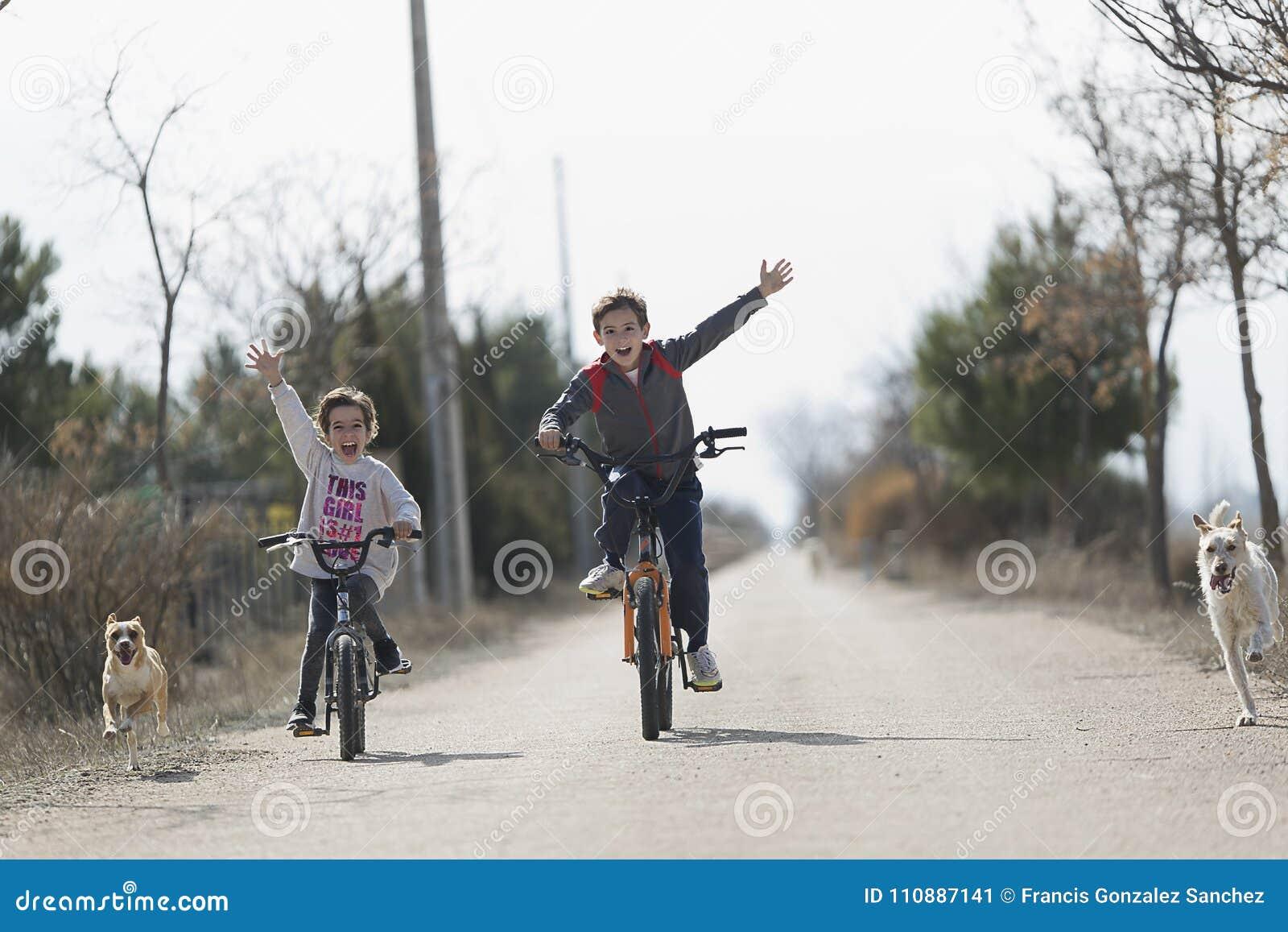 Twee kinderen die met de fiets naar de camera gaan