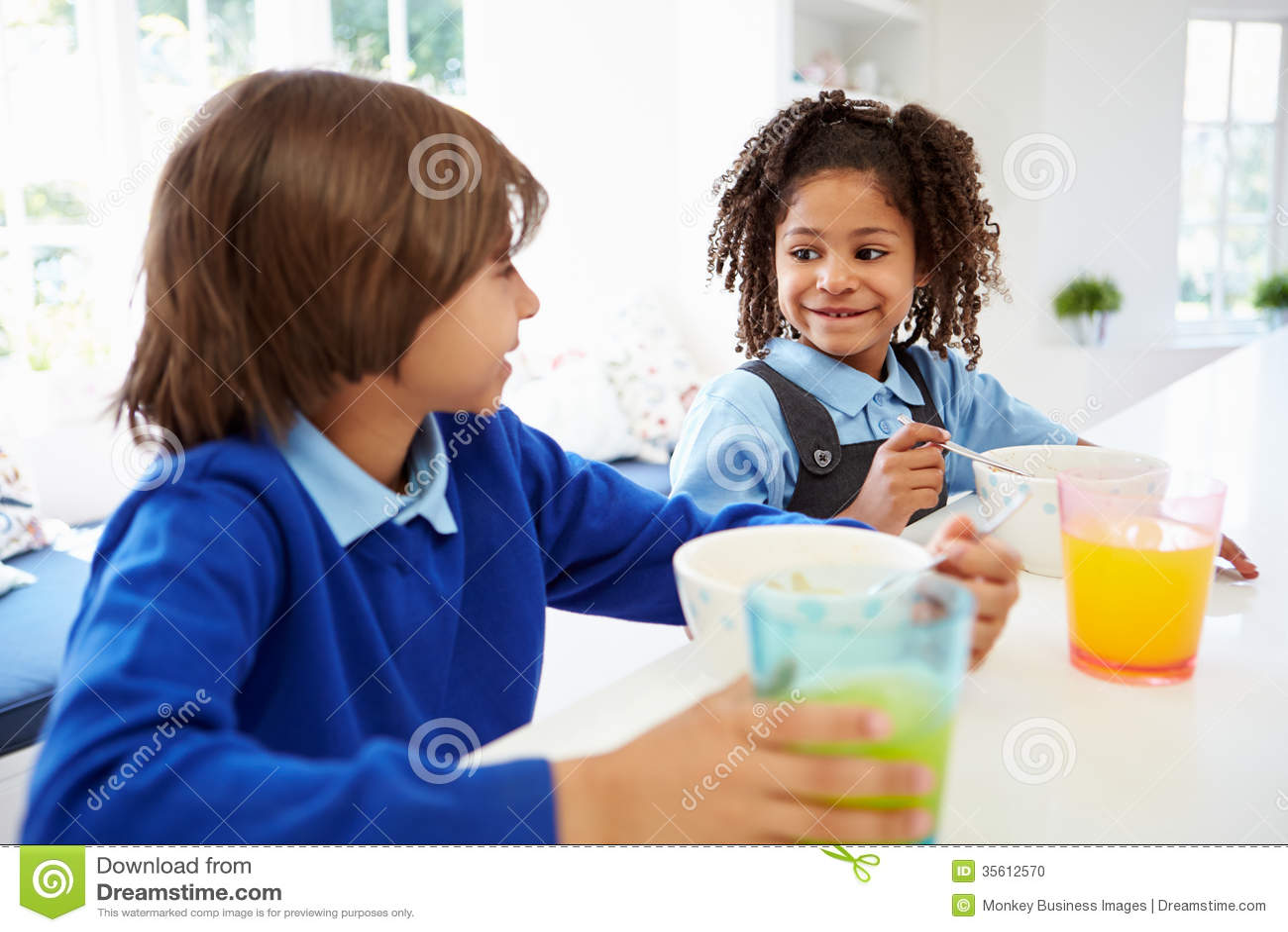 Twee Kinderen die Ontbijt hebben voor School in Keuken