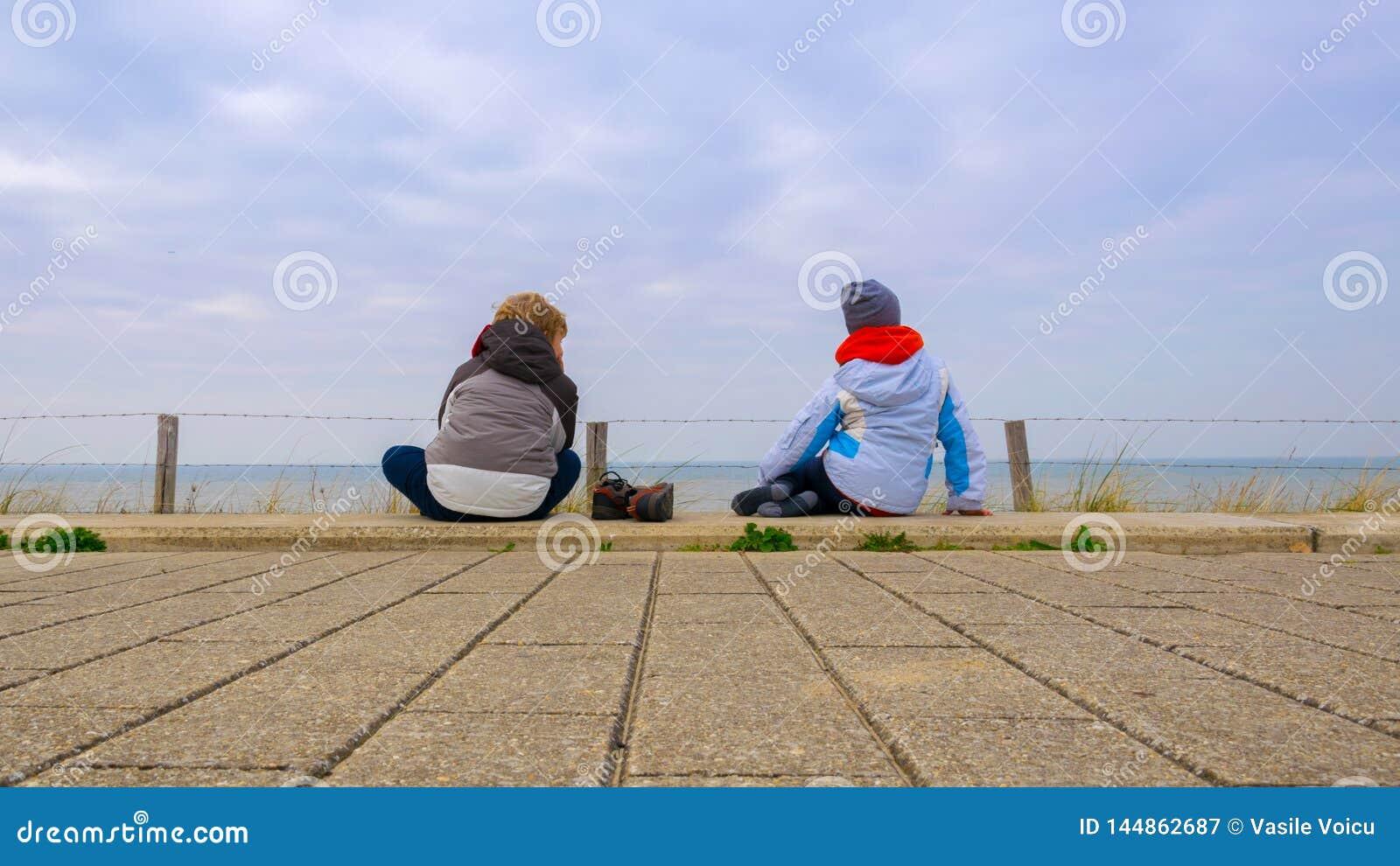 Twee kinderen die op de bestratingen gaan zitten en op het overzees letten, die zich dik met blauwe hemel met witte wolken op de