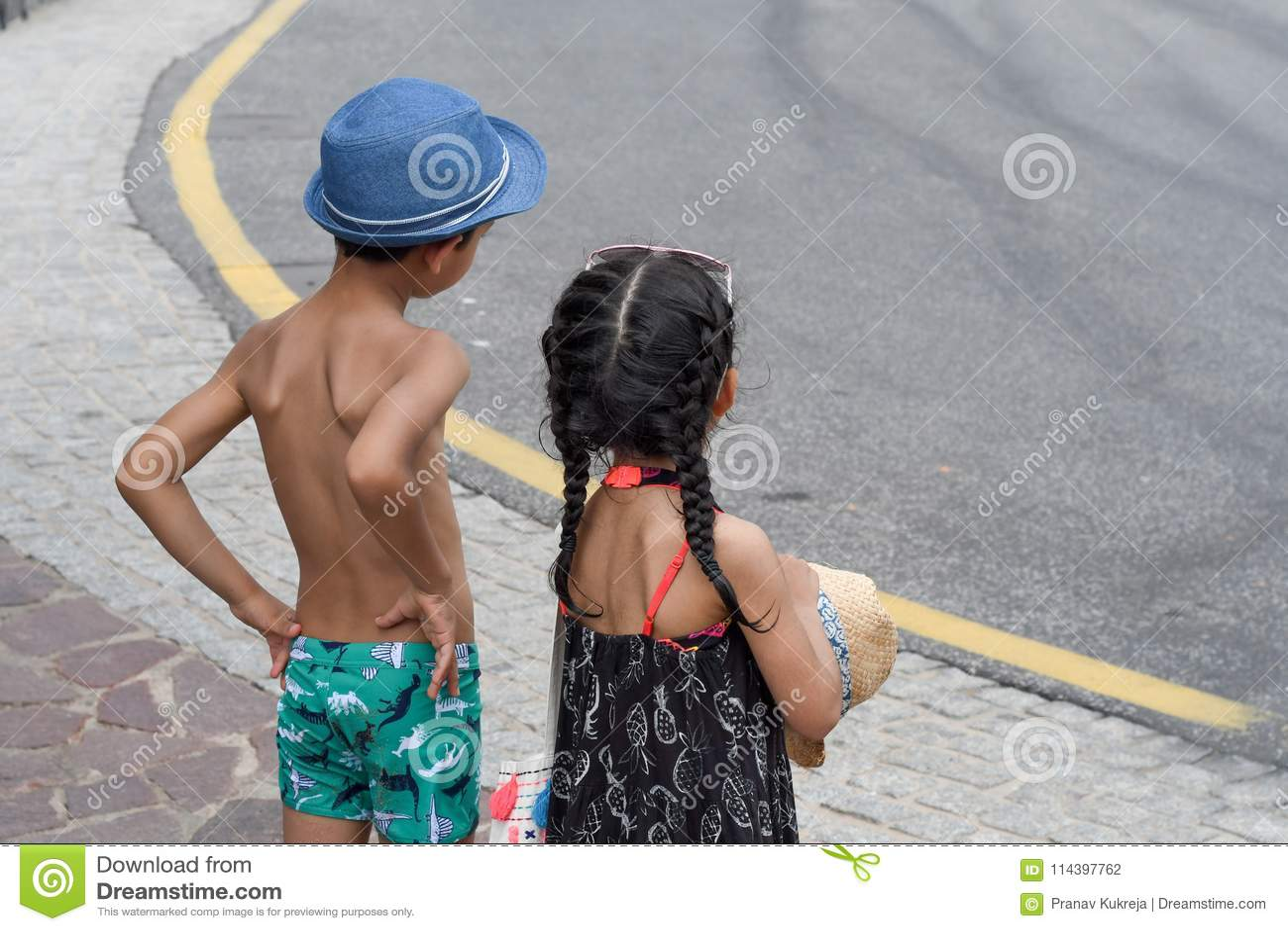 Twee kinderen die zich op kant van de weg bevinden
