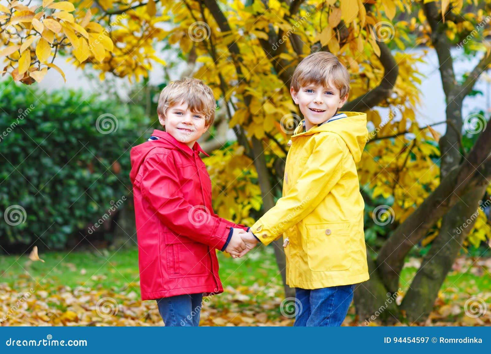 Twee klein beste vrienden en jonge geitjespark van de jongensherfst in kleurrijke kleren