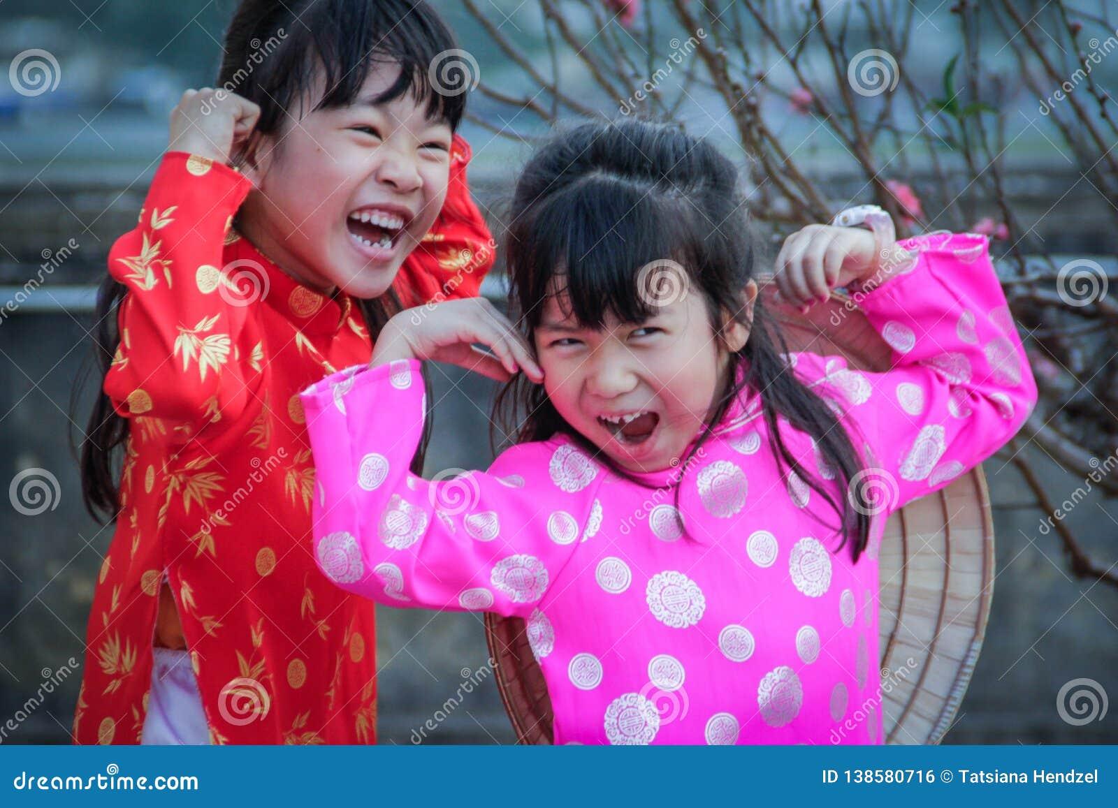 Twee klein Vietnamees meisjesspel en lach in nationale kostuums