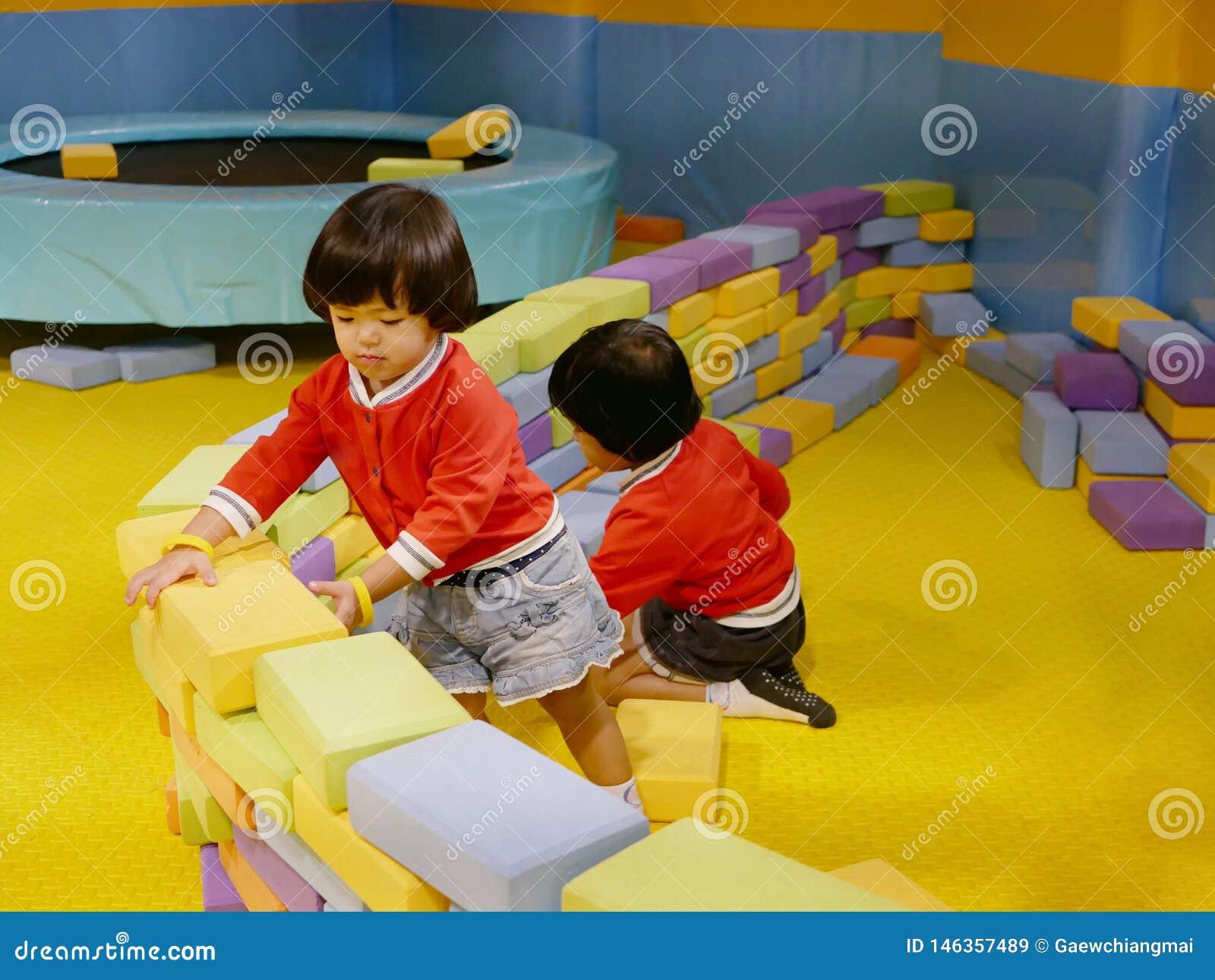 Twee kleine Aziatische babymeisjes, zusters, die omhoog schuim de bouwbakstenen/blokken stapelen samen bij een binnenspeelplaats