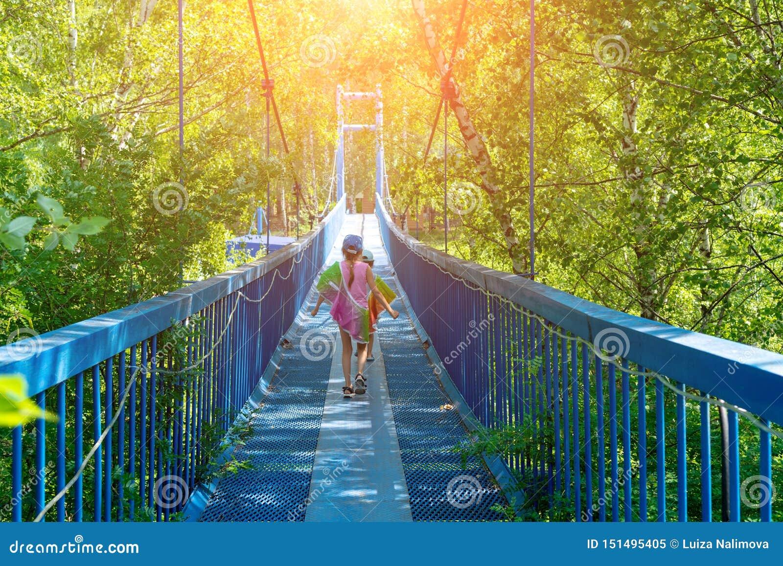 Twee kleine gelukkige meisjesgang langs een hangende brug op een zonnige dag