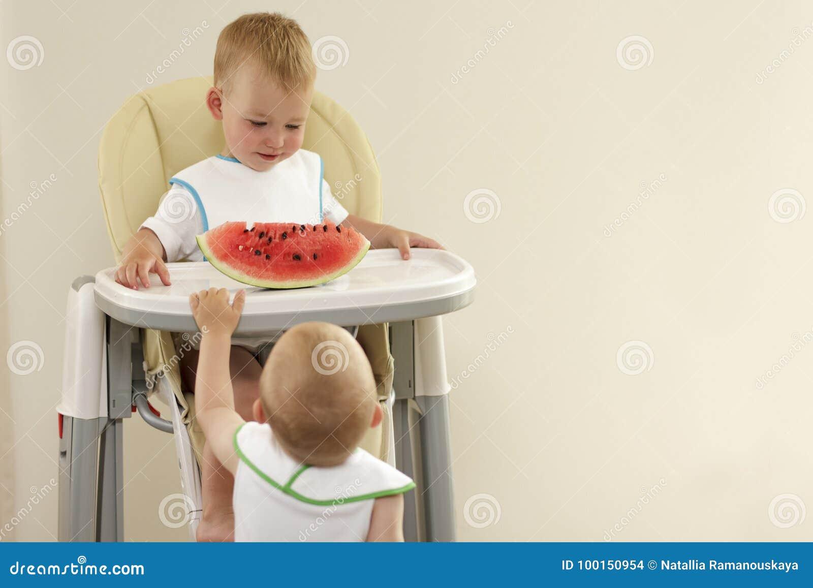 Twee kleine jongens die met blonde haren rode watermeloen eten