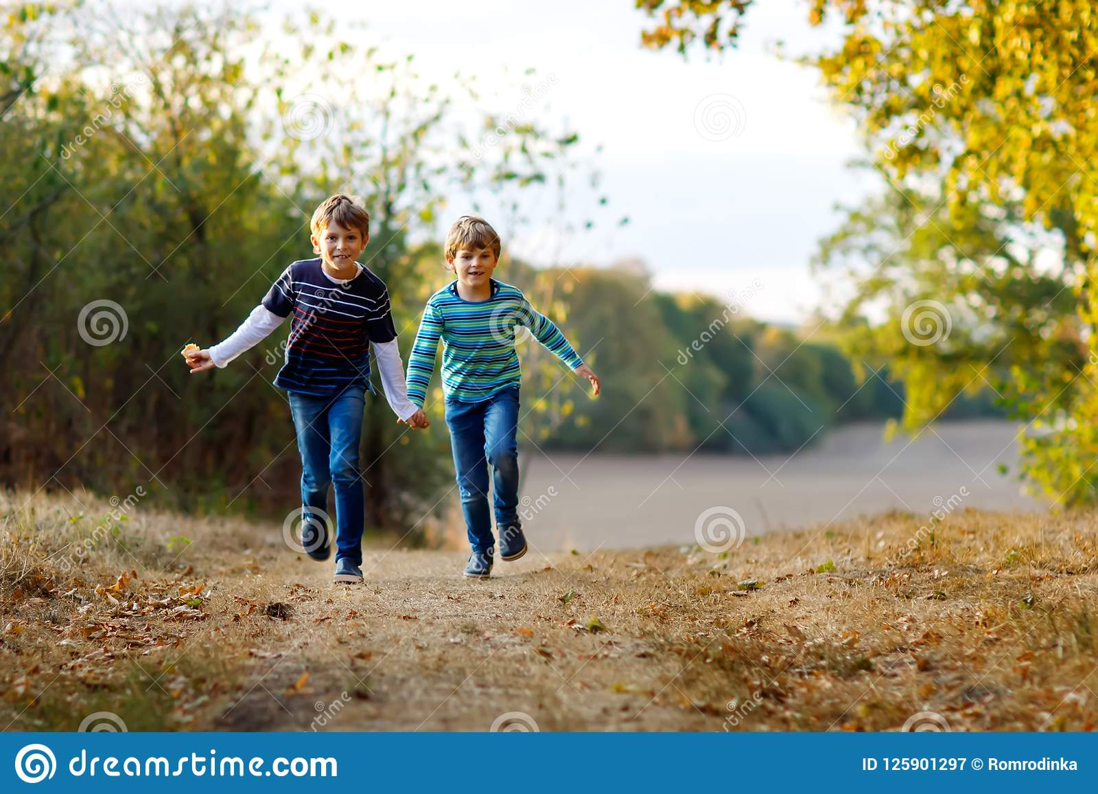 Twee kleine jongens die van schooljonge geitjes en in bos Gelukkige kinderen, beste vrienden en siblings lopen springen die pret