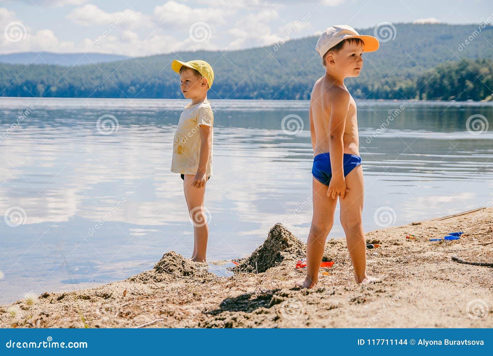Twee kleine jongens in kappen zijn op het meer in de zomer