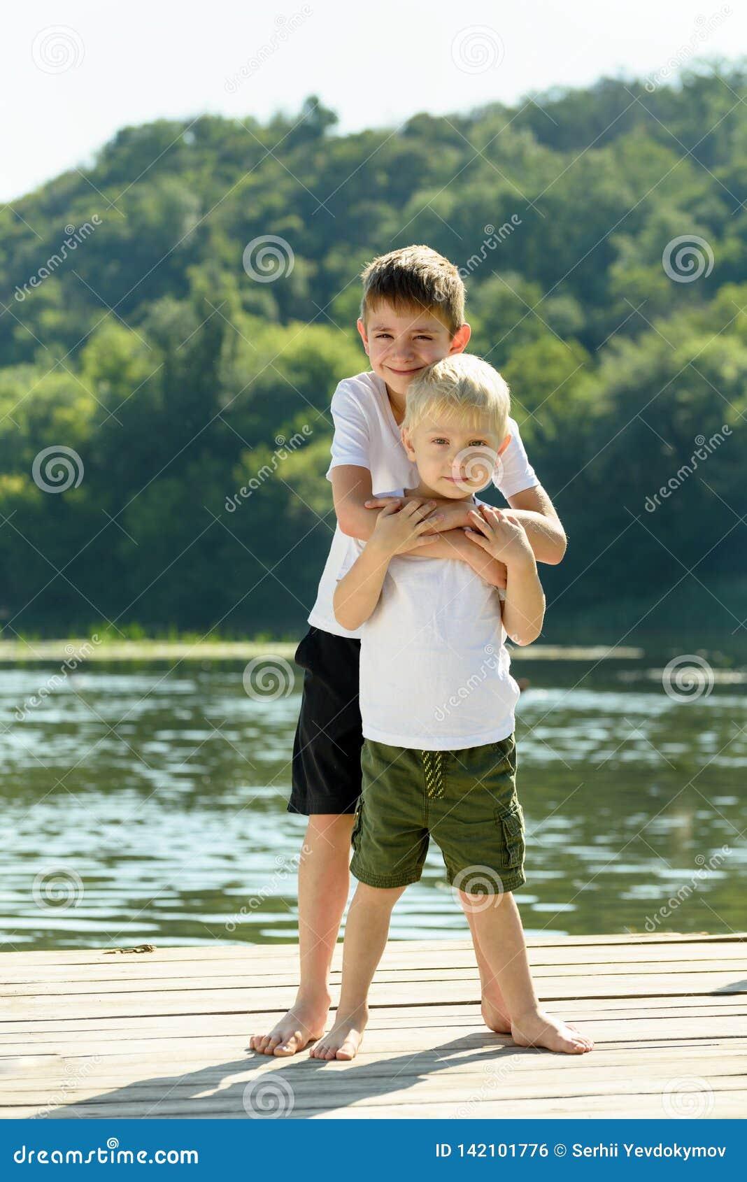 Twee kleine jongens omhelzen op de bank van de rivier Concept vriendschap en broederlijkheid