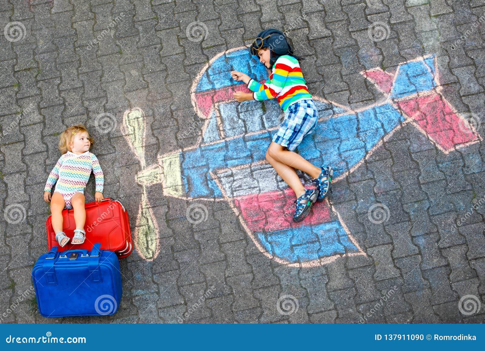 Twee kleine kinderen, jong geitjejongen en peutermeisje die pret met met de tekening van het vliegtuigbeeld met kleurrijk krijt h