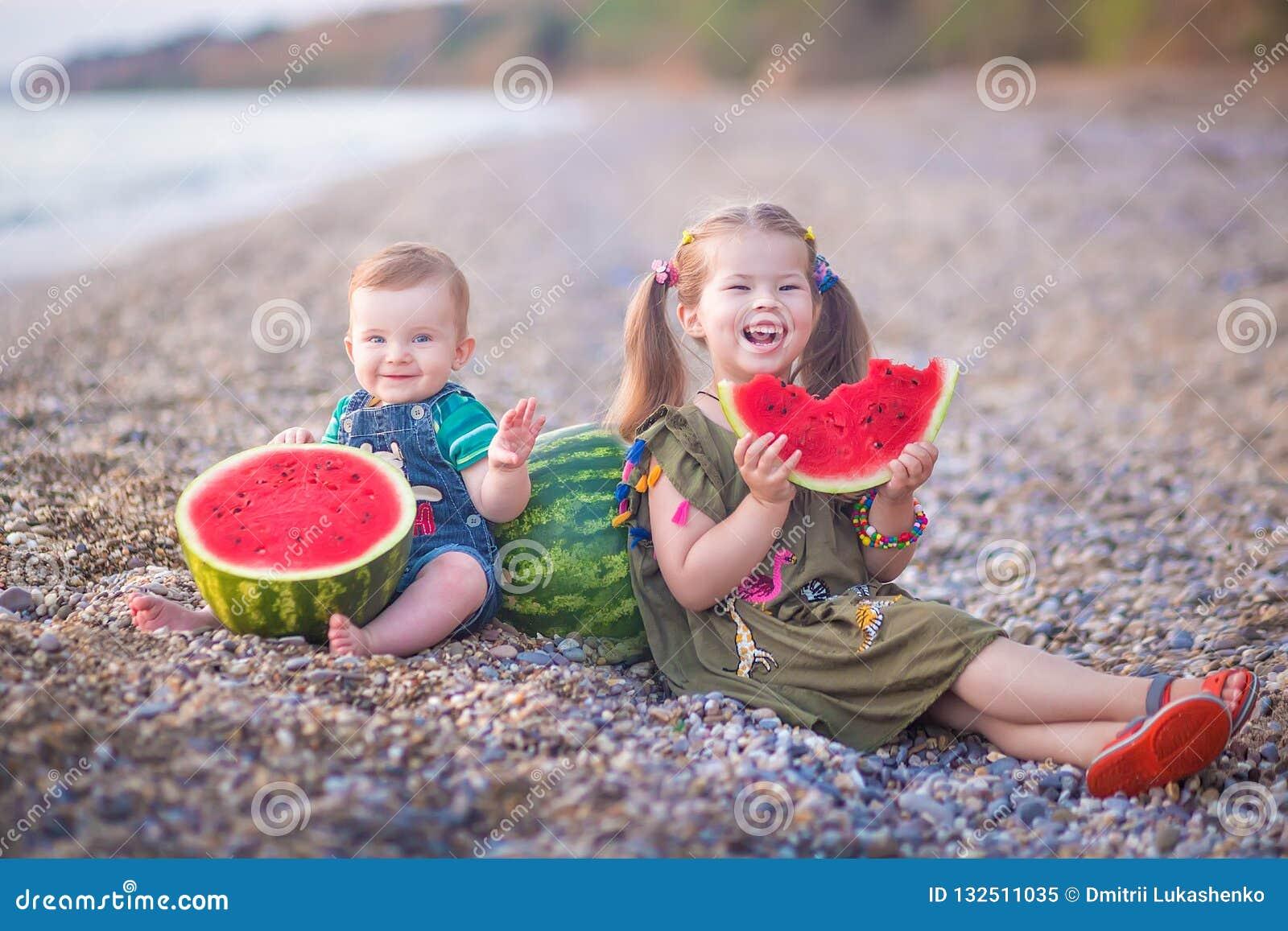 Twee kleine kinderen, jongensmeisje, die watermeloen op het strand eten, zomer die van mooie dag dicht bij oceaan genieten