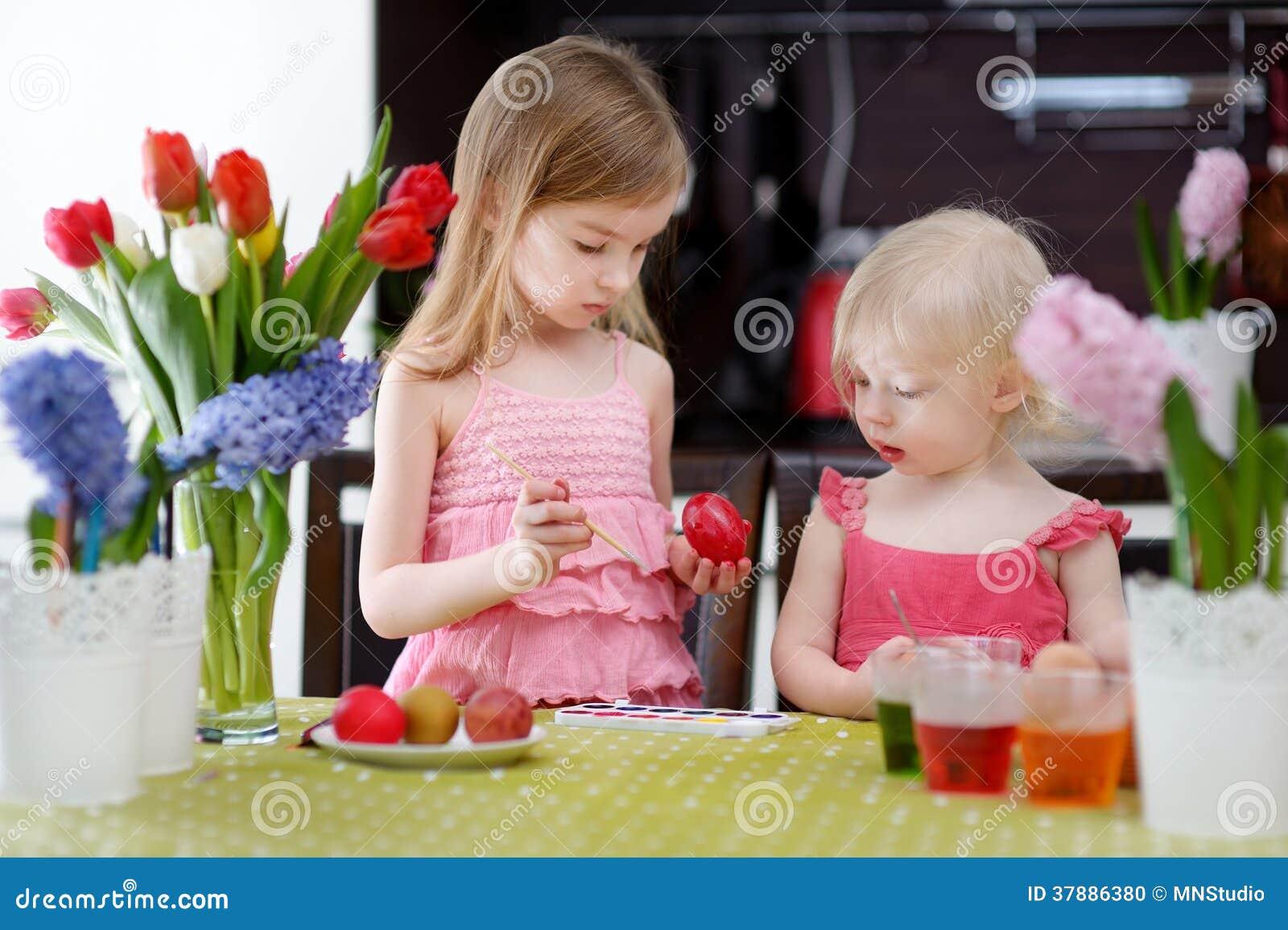 Twee kleine zusters die paaseieren schilderen