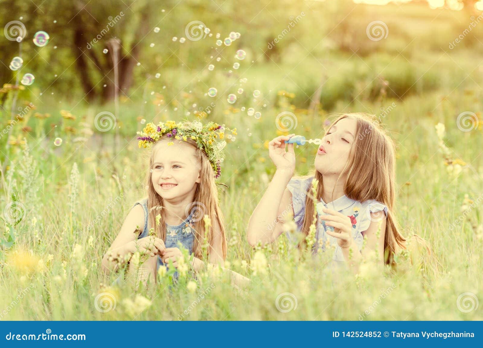 Twee kleine zusters die zeepbels blazen