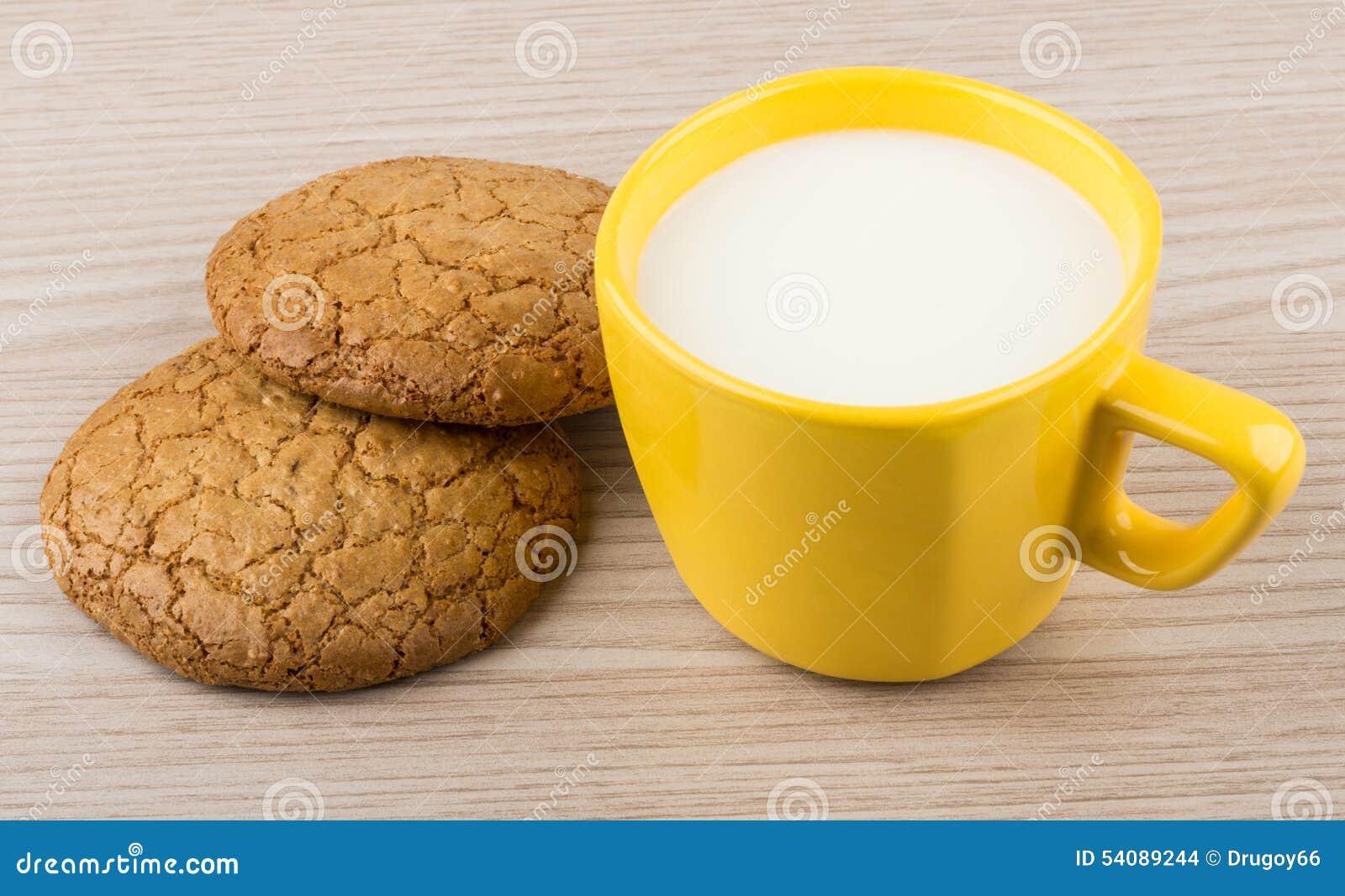 Twee koekjes en kop van melk op lijst