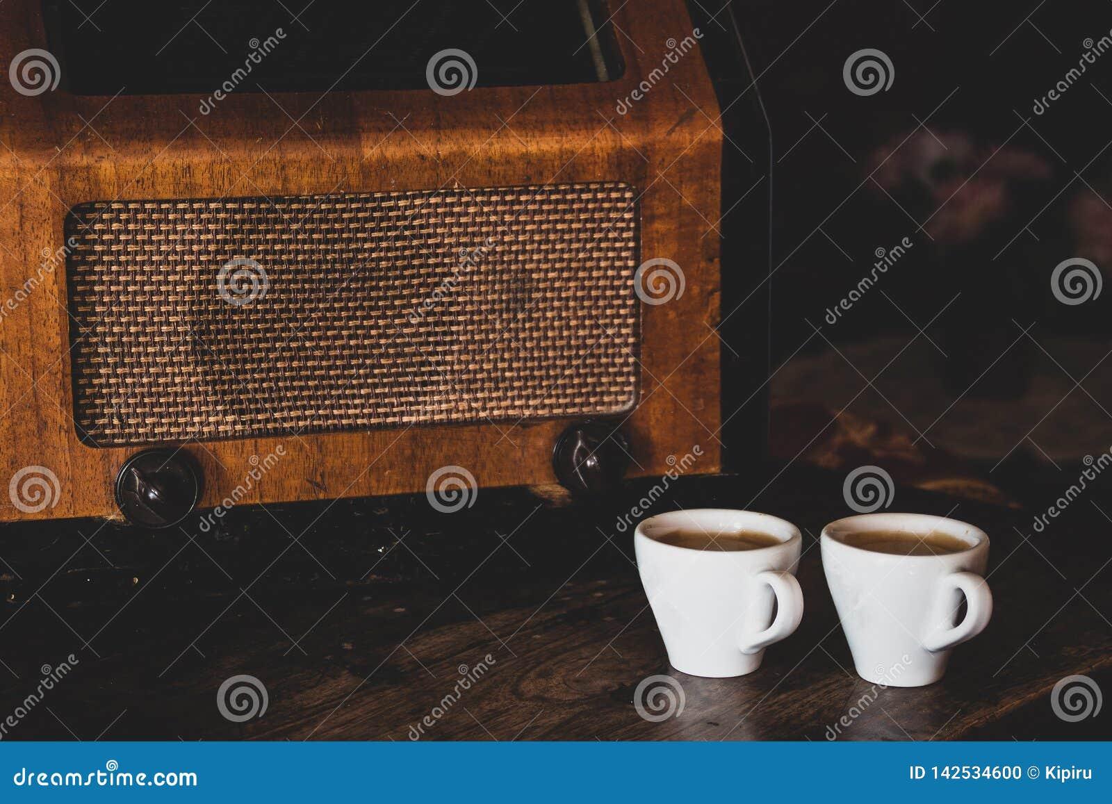 Twee koffiekoppen met espresso en retro radio op donkere houten achtergrond Uitstekende kleurentoon