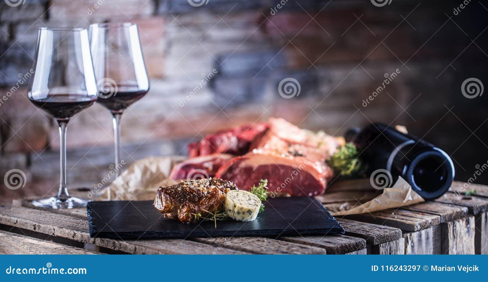Twee koppen met rode geroosterde wijn en ruw rundvleeslapje vlees op leiraad