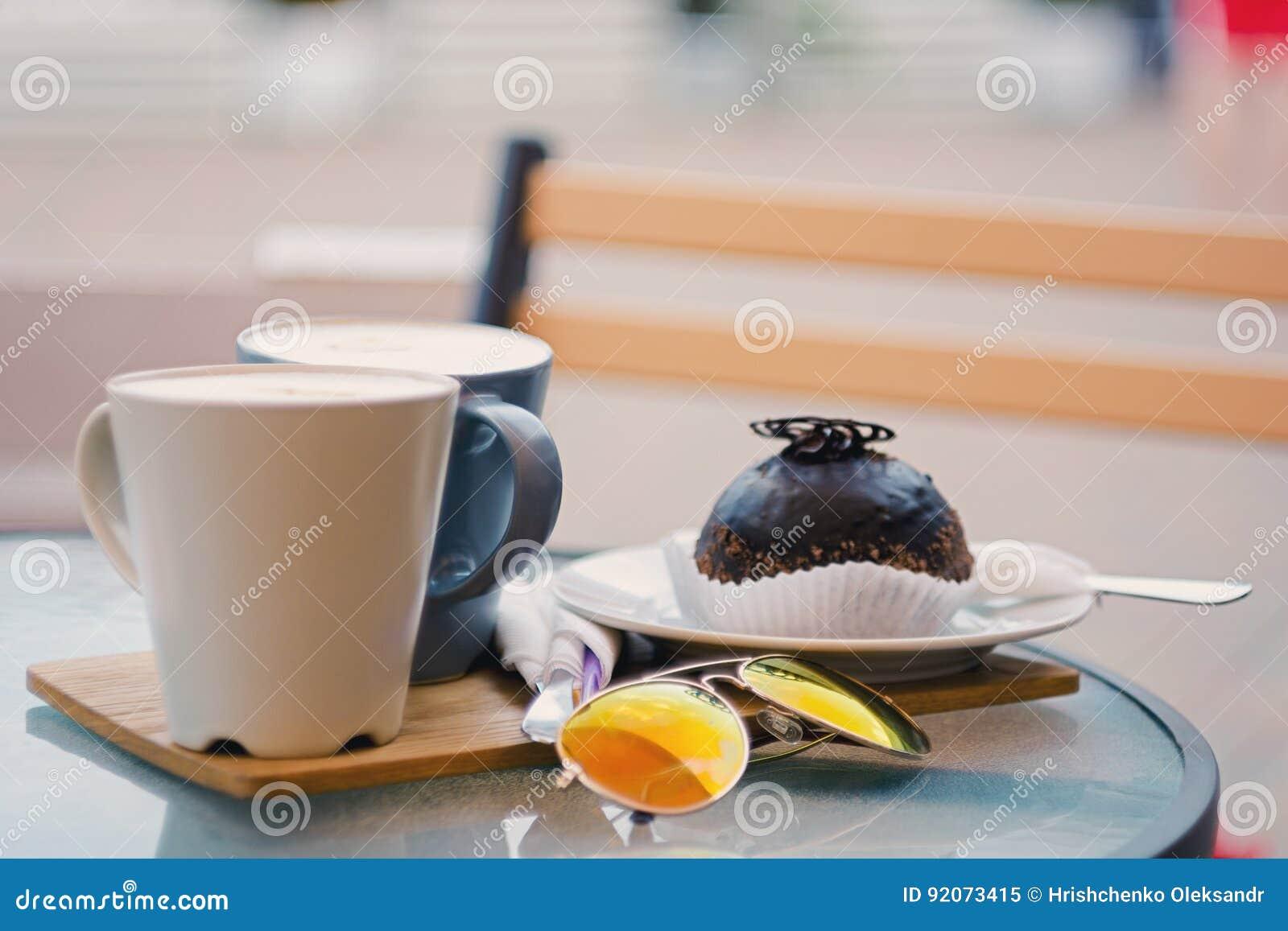 Twee koppen van koffie en een chocoladecake op de lijst