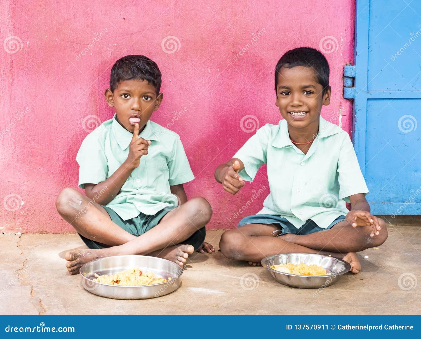 Twee leerlingen die van Jongenstieners gediende Maaltijdplaat van rijst in de Kantine van de overheidsschool zijn Ongezond voedse