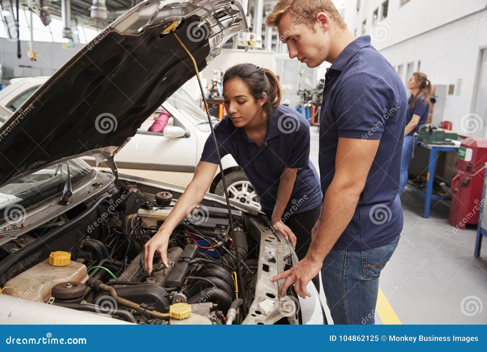 Twee leerlingswerktuigkundigen die de motor in een auto bekijken