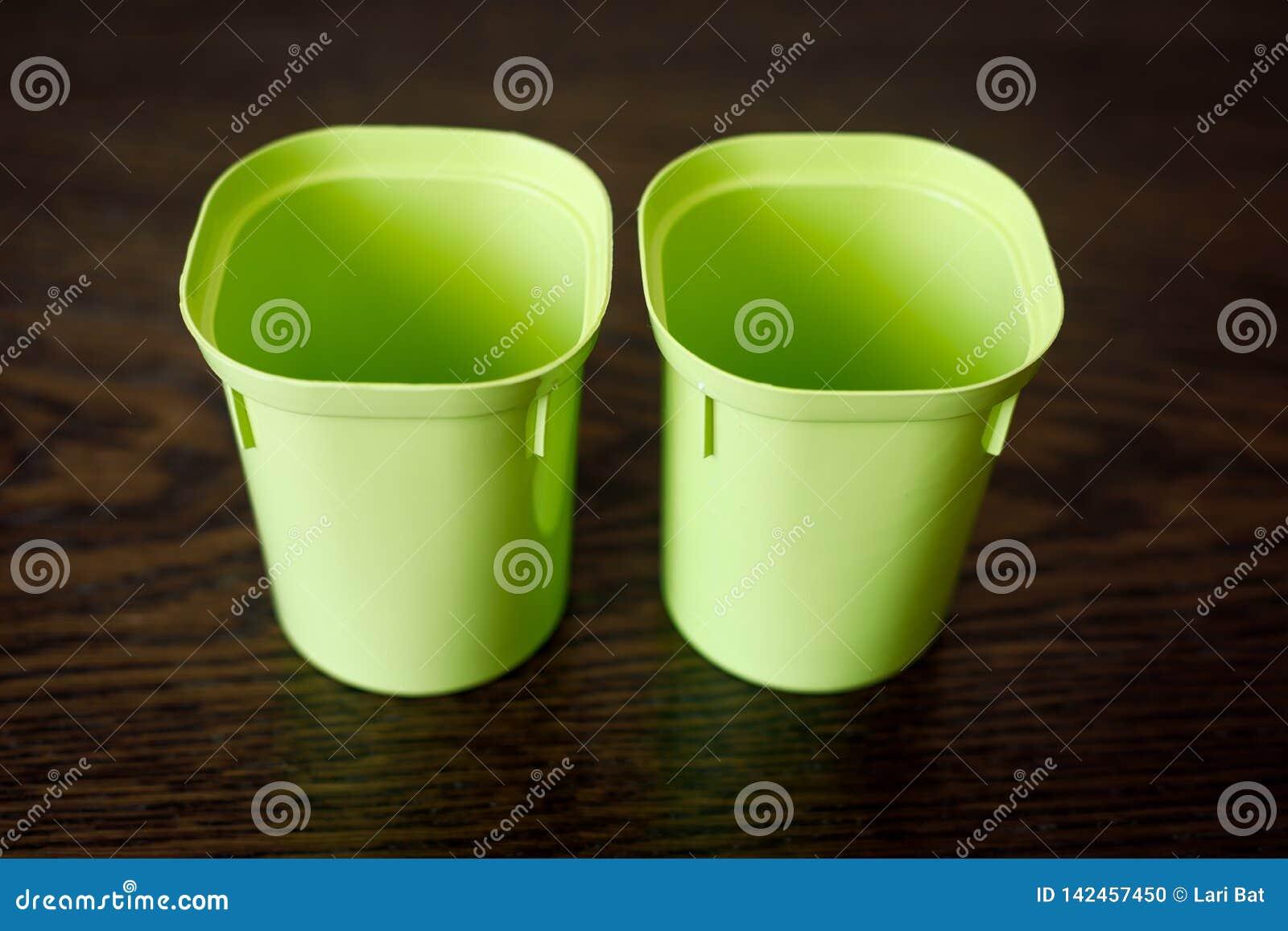 Twee lege plastic koppen voor zaailingen Bloementeeltpunten