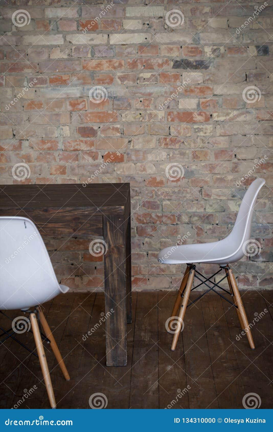 Twee lege witte houten voetenbanken dichtbij de houten lijst in het zolderbinnenland met houten vloer