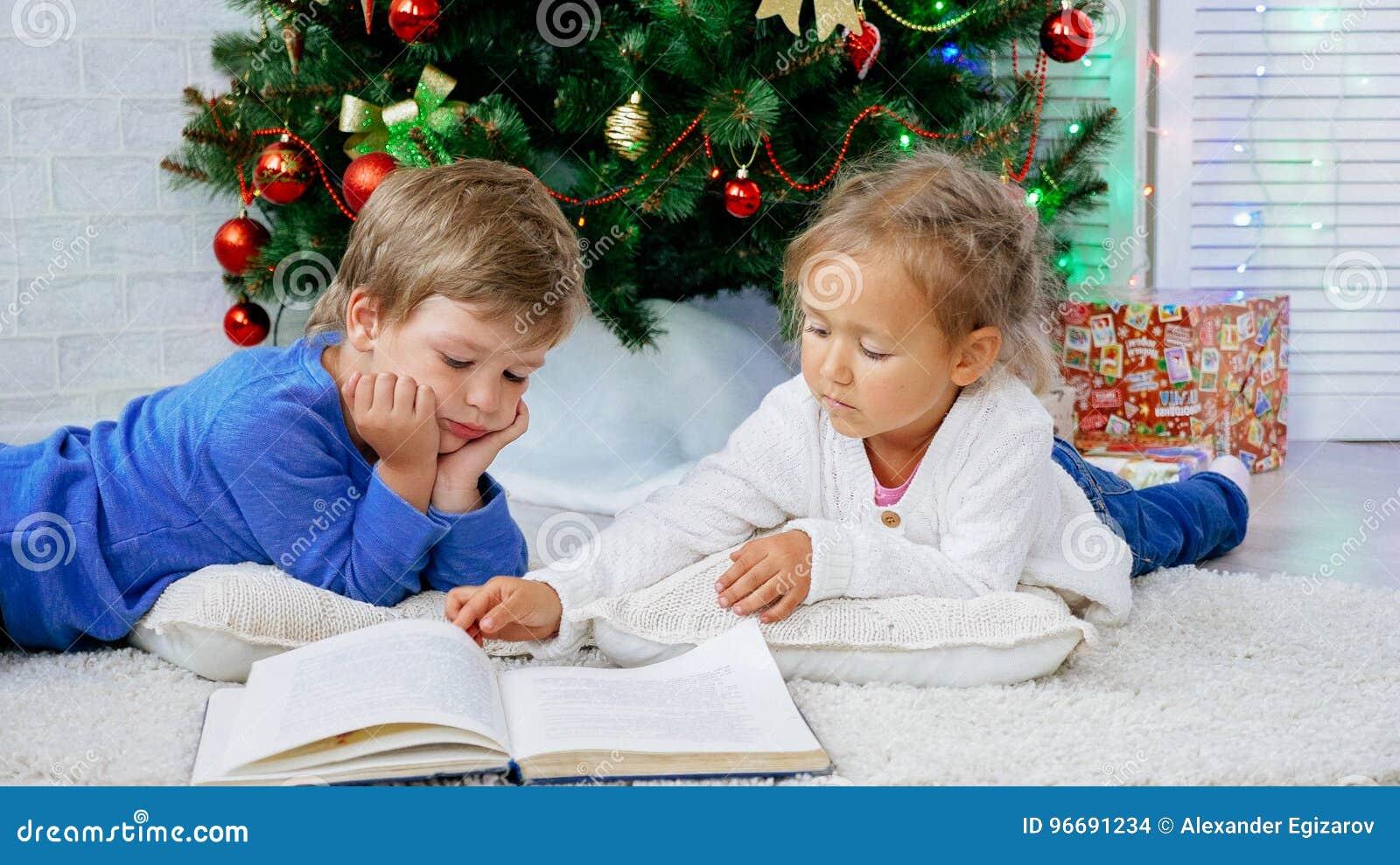 Twee leuke childes die op de vloer liggen en boek lezen bij Kerstmisvooravond