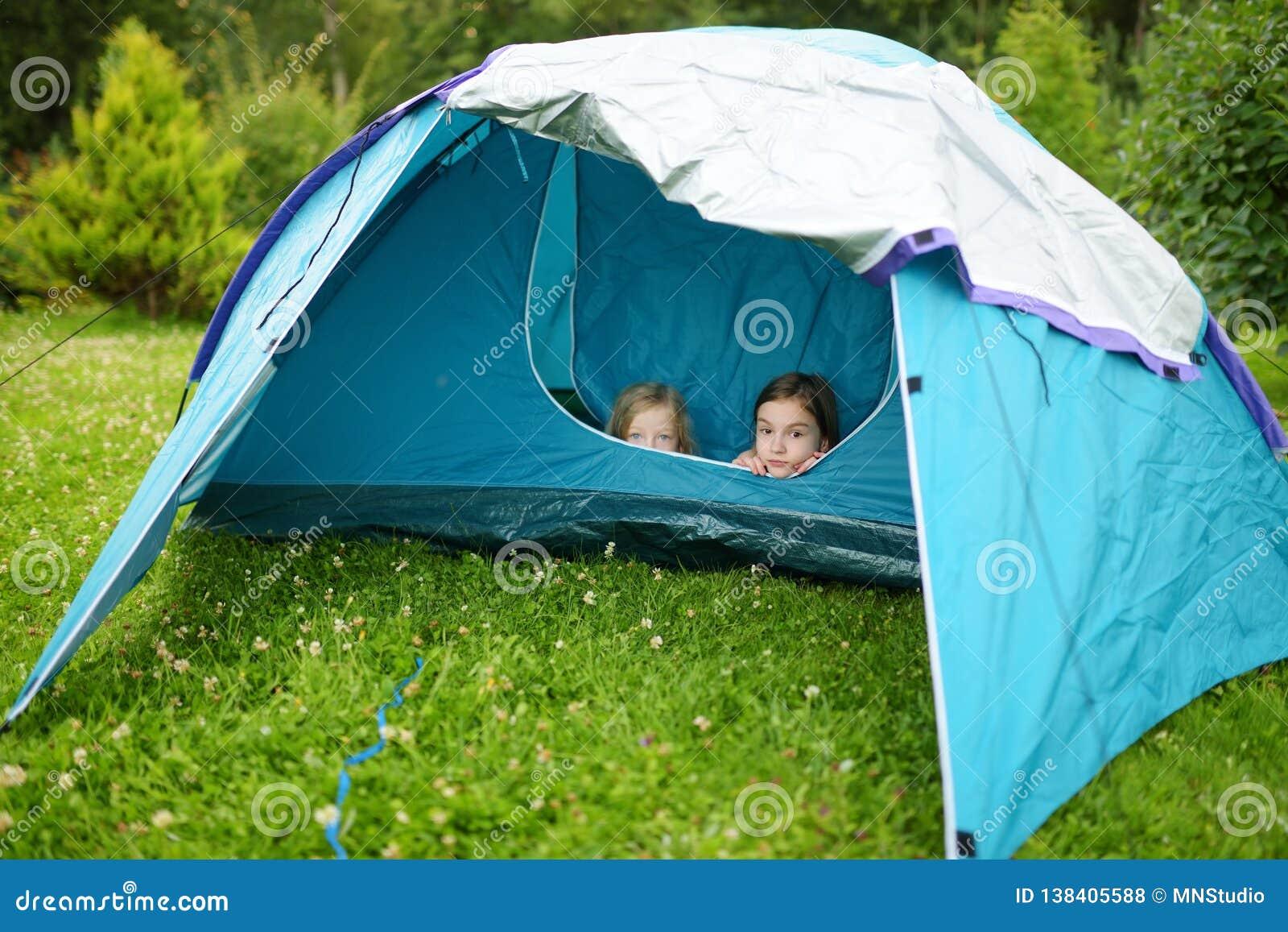 Twee leuke jonge zusters die in een tent op een kampeerterrein spelen Actieve levensstijl, familie recreatief weekend, de zomer o