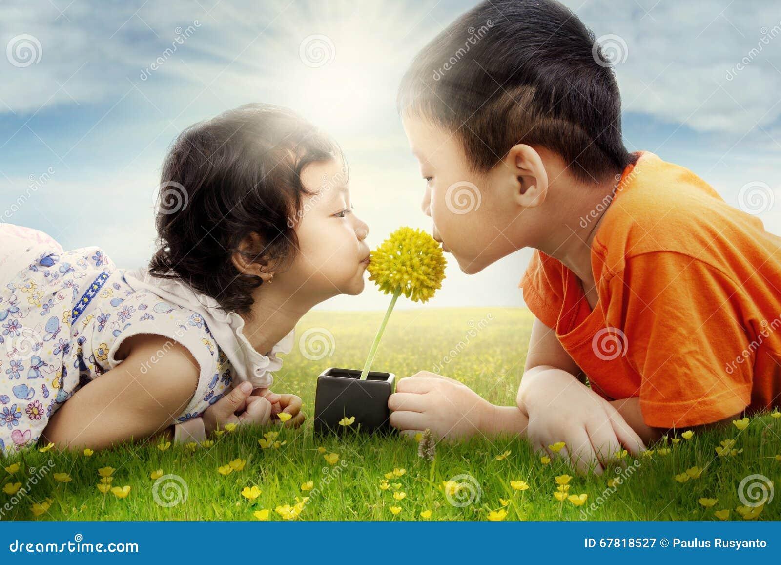 Kussen Voor Kinderen : Twee leuke kinderen die bloem kussen bij gebied stock afbeelding
