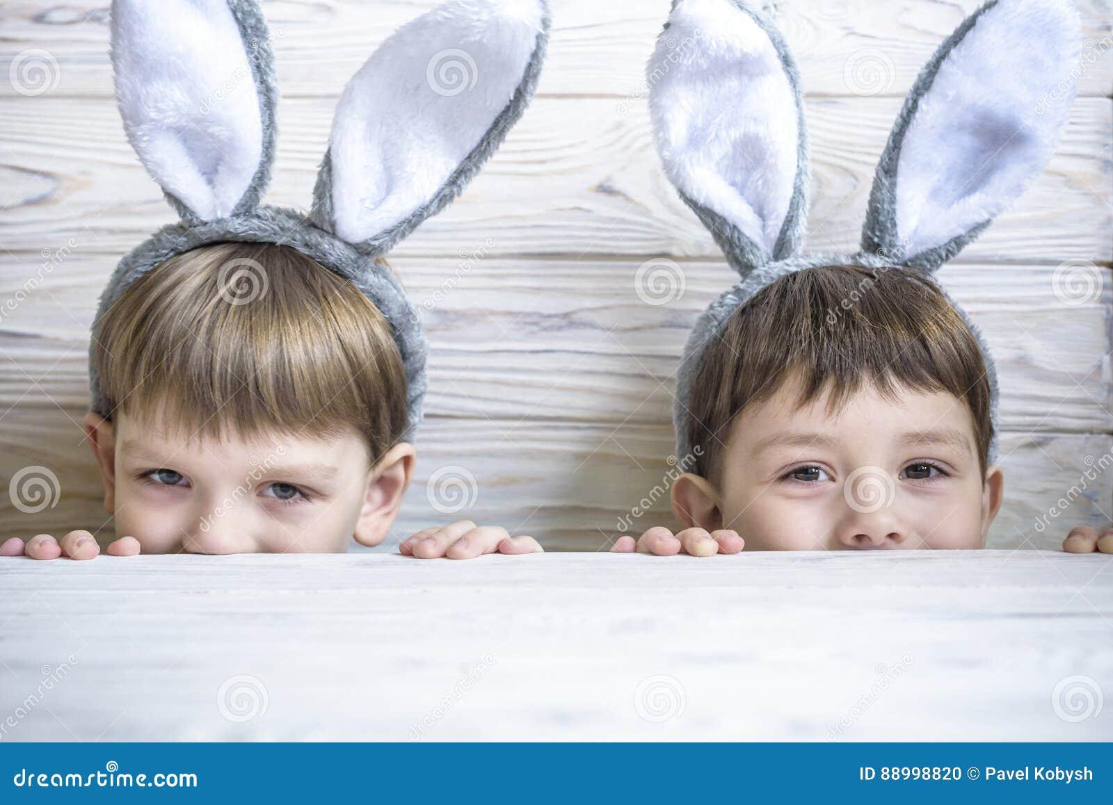 Twee leuke kleine broers die konijntjesoren dragen die eijacht op Pasen spelen De aanbiddelijke kinderen vieren thuis Pasen