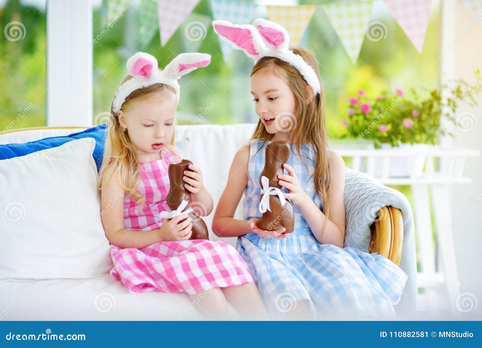 Twee leuke kleine zusters die konijntjesoren dragen die de konijnen van chocoladepasen eten Jonge geitjes die eijacht op Pasen sp