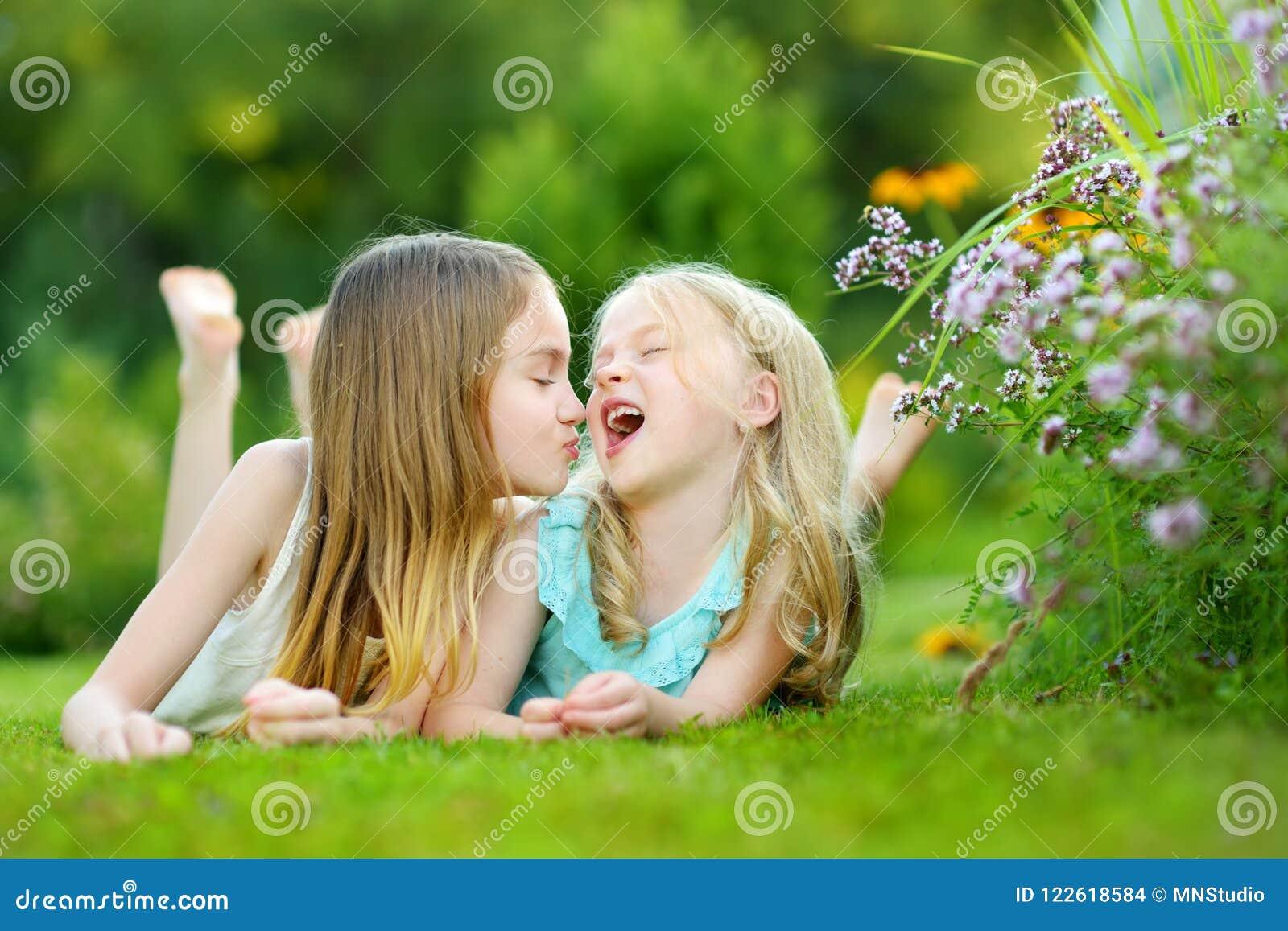 Twee leuke kleine zusters die pret samen op het gras op een zonnige de zomerdag hebben