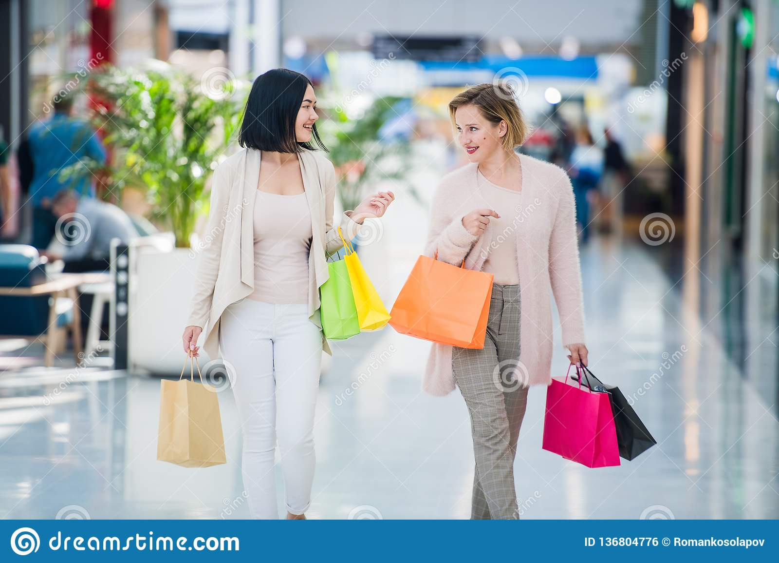 Twee leuke meisjesgangen in de Wandelgalerij met giftzakken Gelukkig en glimlachend na het winkelen met heel wat aankopen