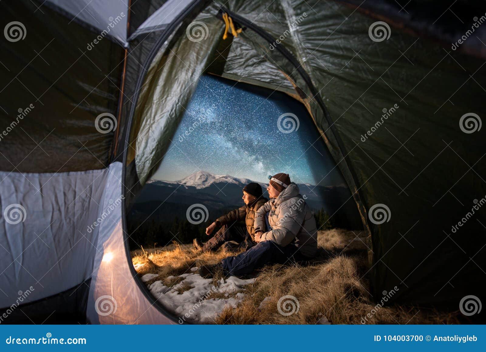 Twee mannelijke toeristen hebben een rust in het kamperen in de bergen bij nacht onder het hoogtepunt van de nachthemel van sterr