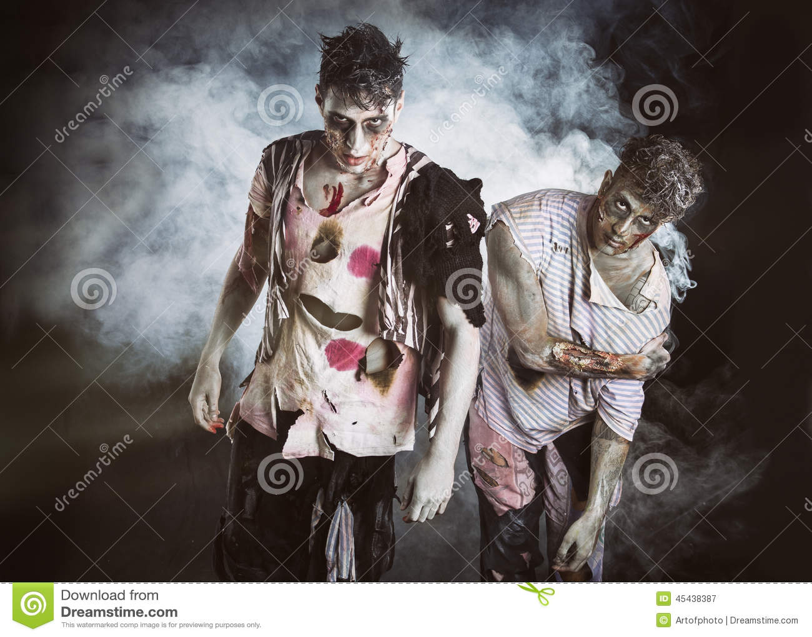 Twee mannelijke zombieën die zich op zwarte rokerige achtergrond bevinden
