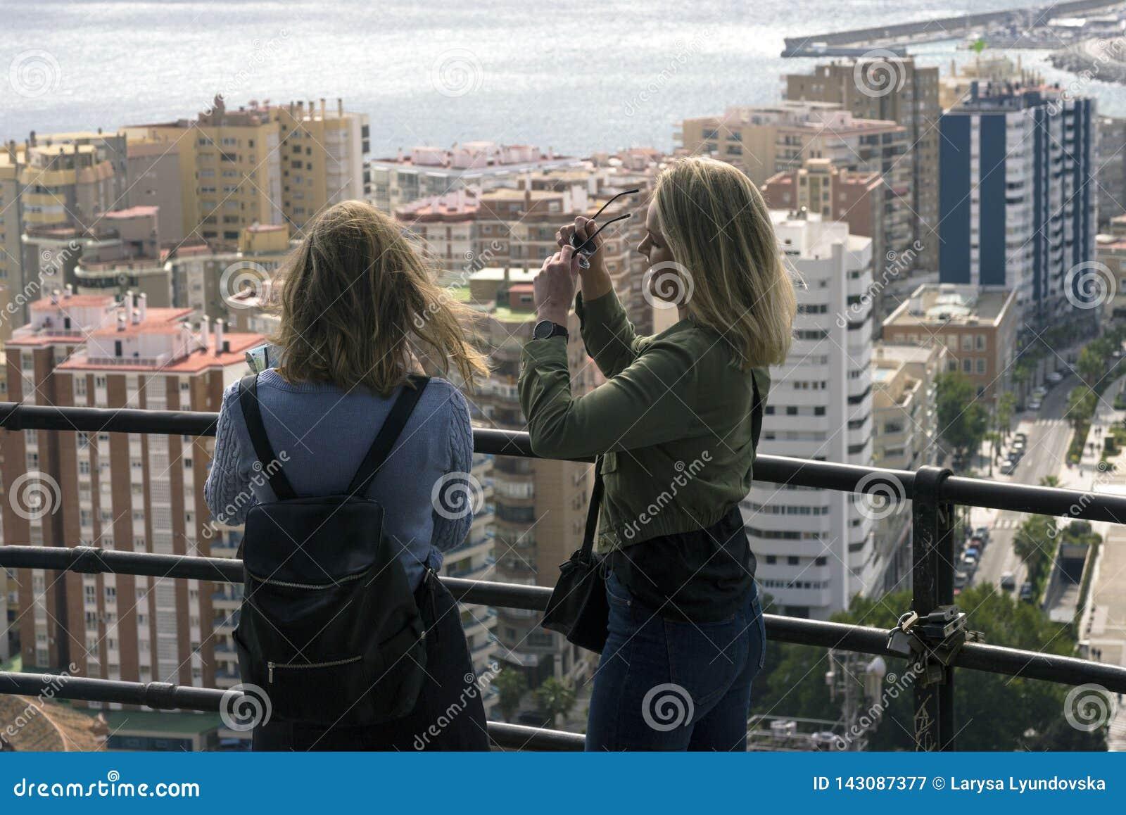 Twee meisjes bevinden zich op een heuvel en bekijken het mooie panorama van de Spaanse stad van Malaga op warm