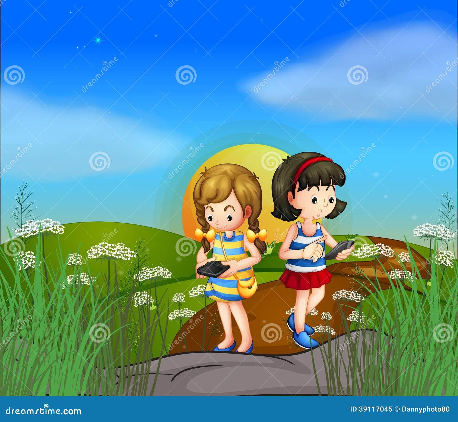 Twee meisjes bij de heuveltop die hun cellphones gebruiken