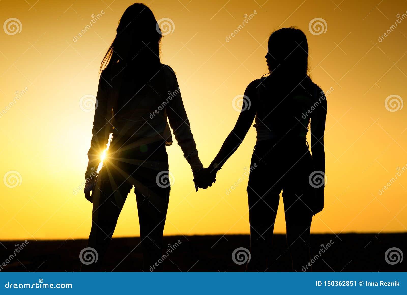 Twee meisjes die elkaar houden overhandigt De dames koppelen op het strand