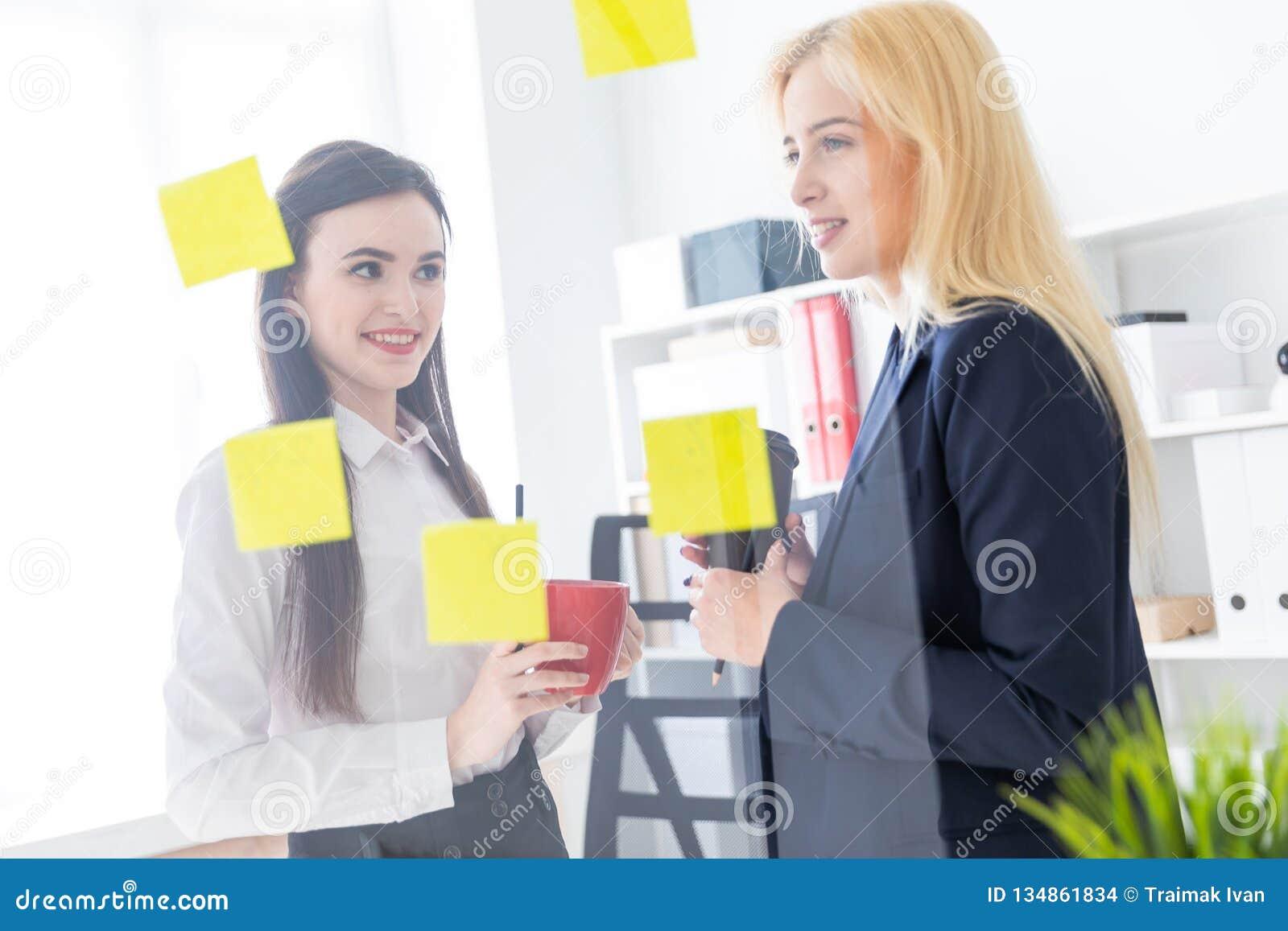 Twee meisjes die in het bureau spreken De meisjes zijn een dialoog dichtbij een transparante Raad met stickers