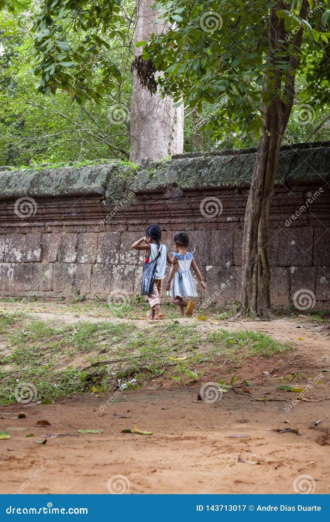 Twee meisjes die langs een steenmuur lopen