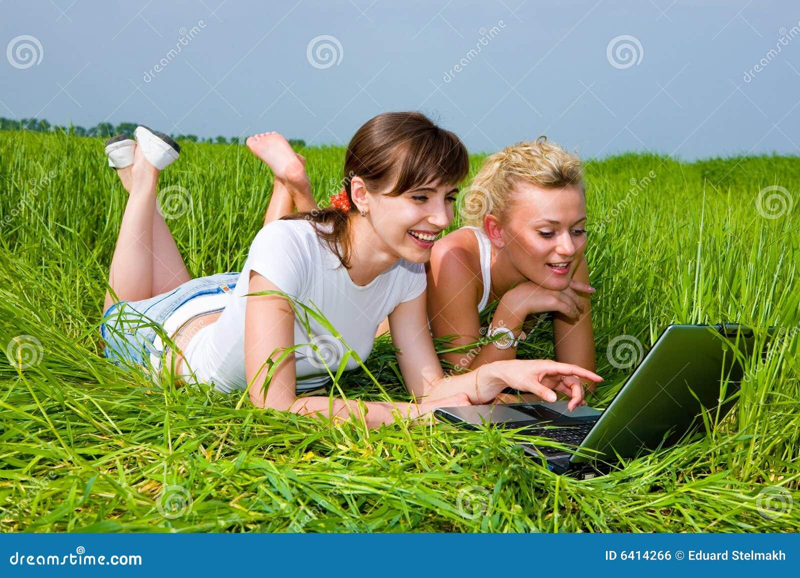 Twee meisjes die laptop computer bekijken