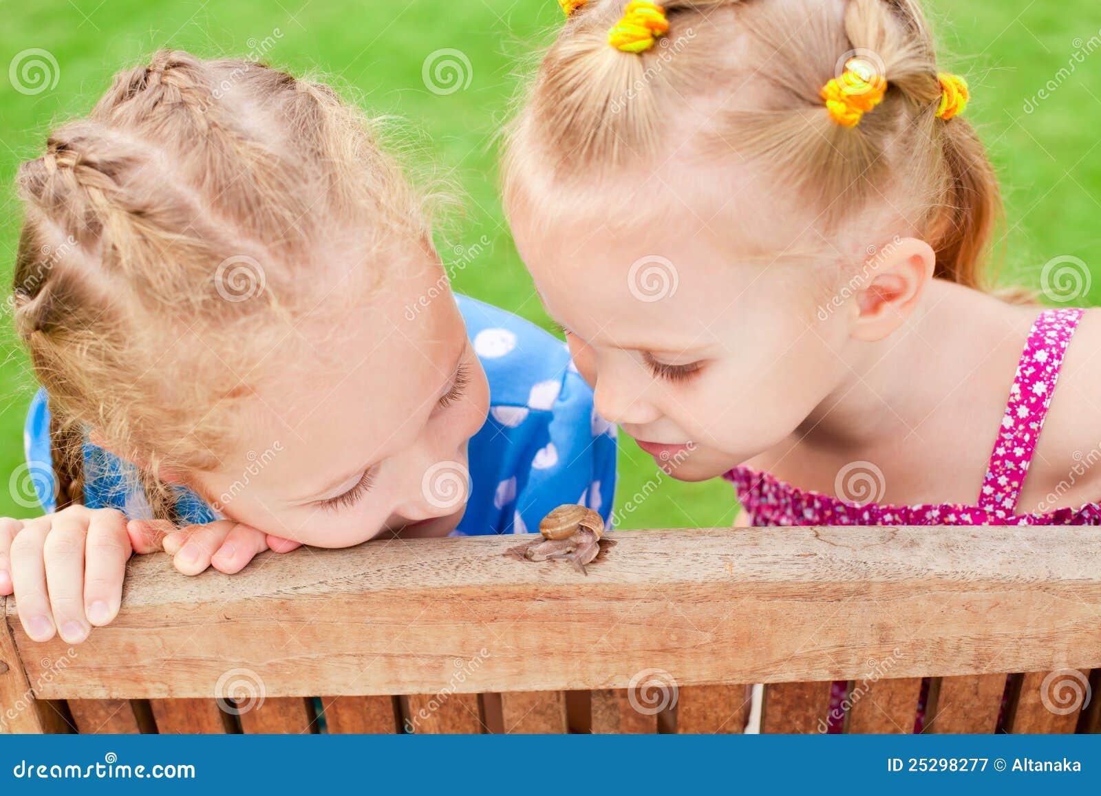 Twee meisjes die op een slak letten