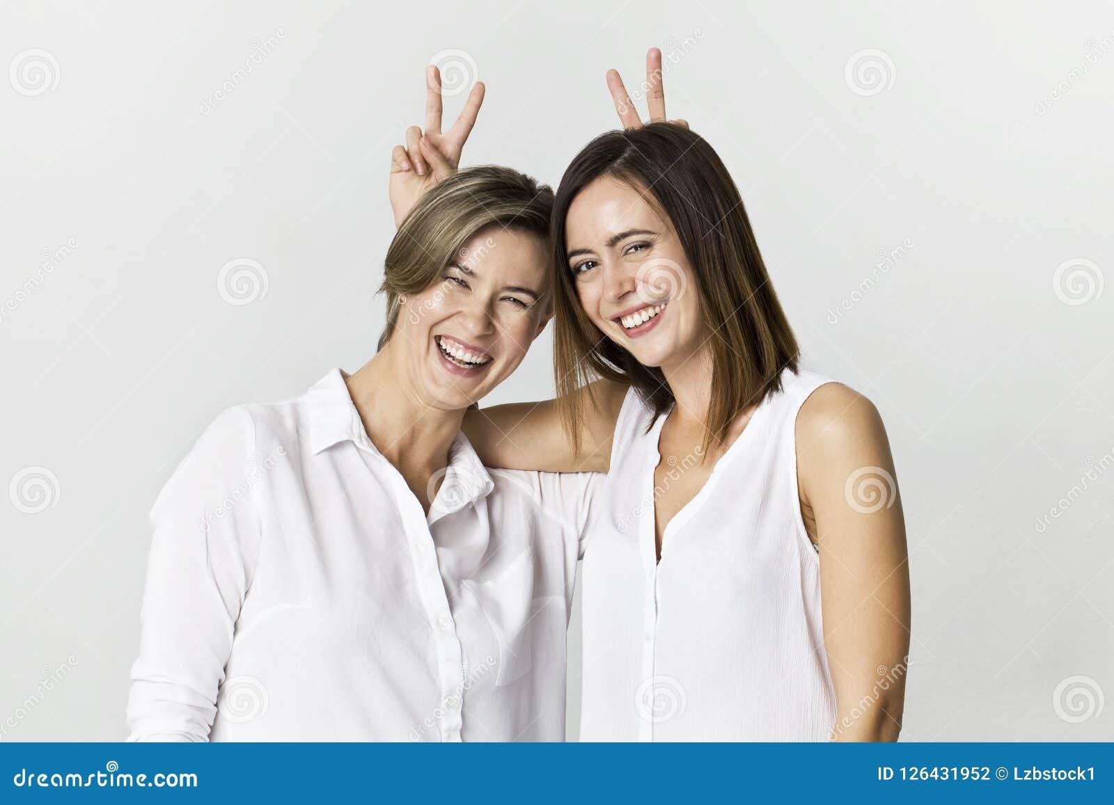 Twee meisjes die pret hebben bij studioachtergrond Toothy het glimlachen twee jong vrouwenportret