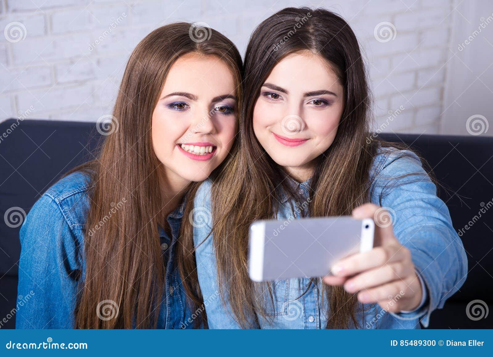 Twee meisjes die selfie foto met slimme telefoon nemen
