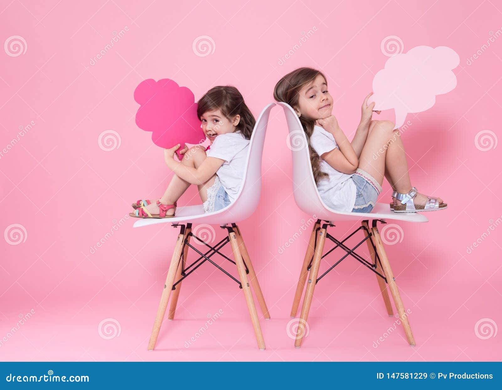 Twee meisjes op een gekleurde achtergrond met toespraakpictogrammen