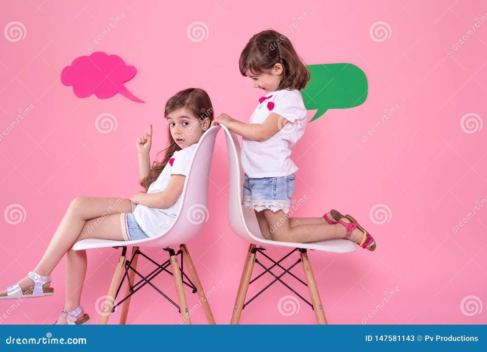 Twee meisjes op gekleurde achtergrond met toespraakpictogrammen