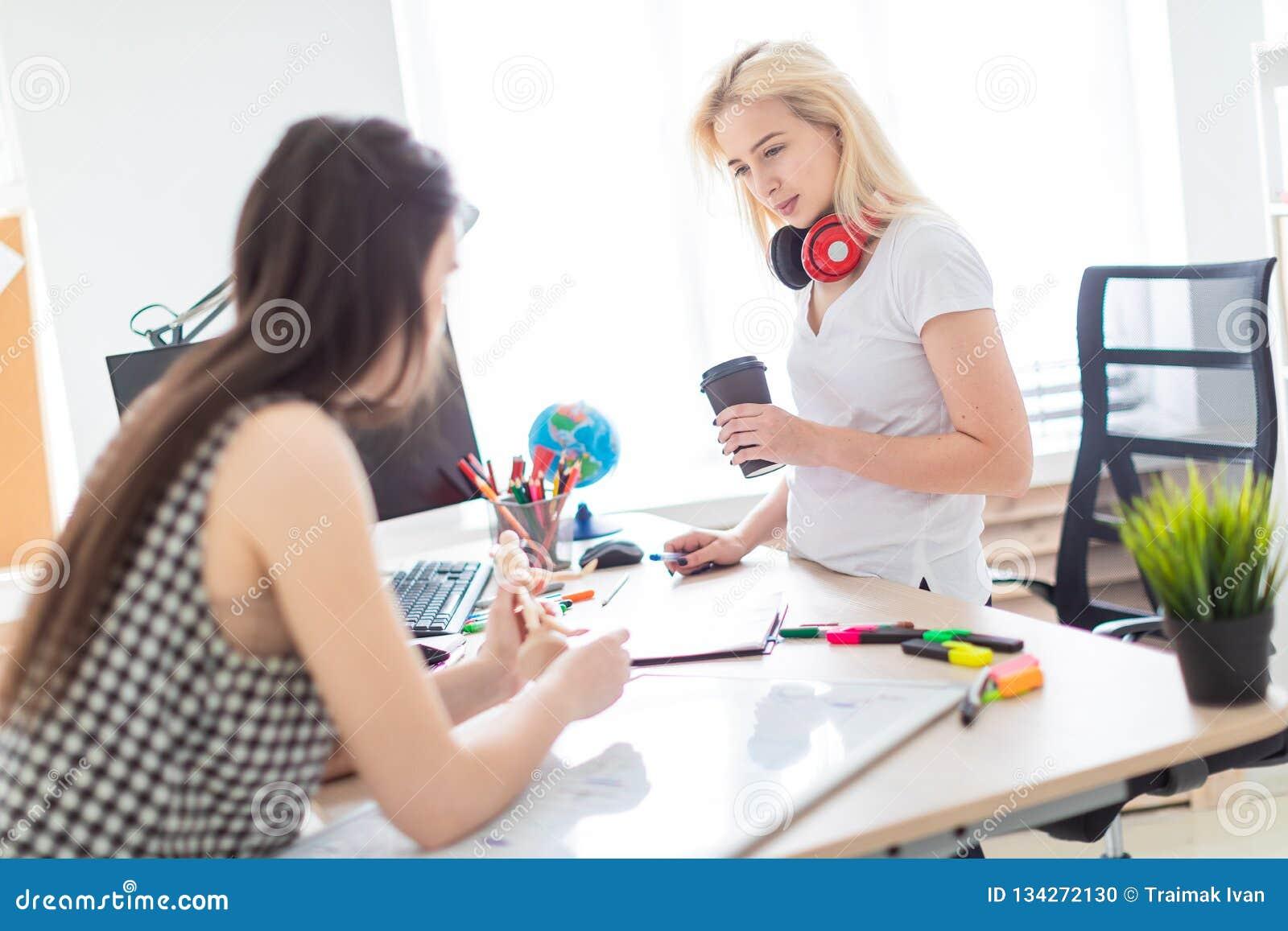 Twee meisjes werken in het bureau Het meisje houdt een model van een mens