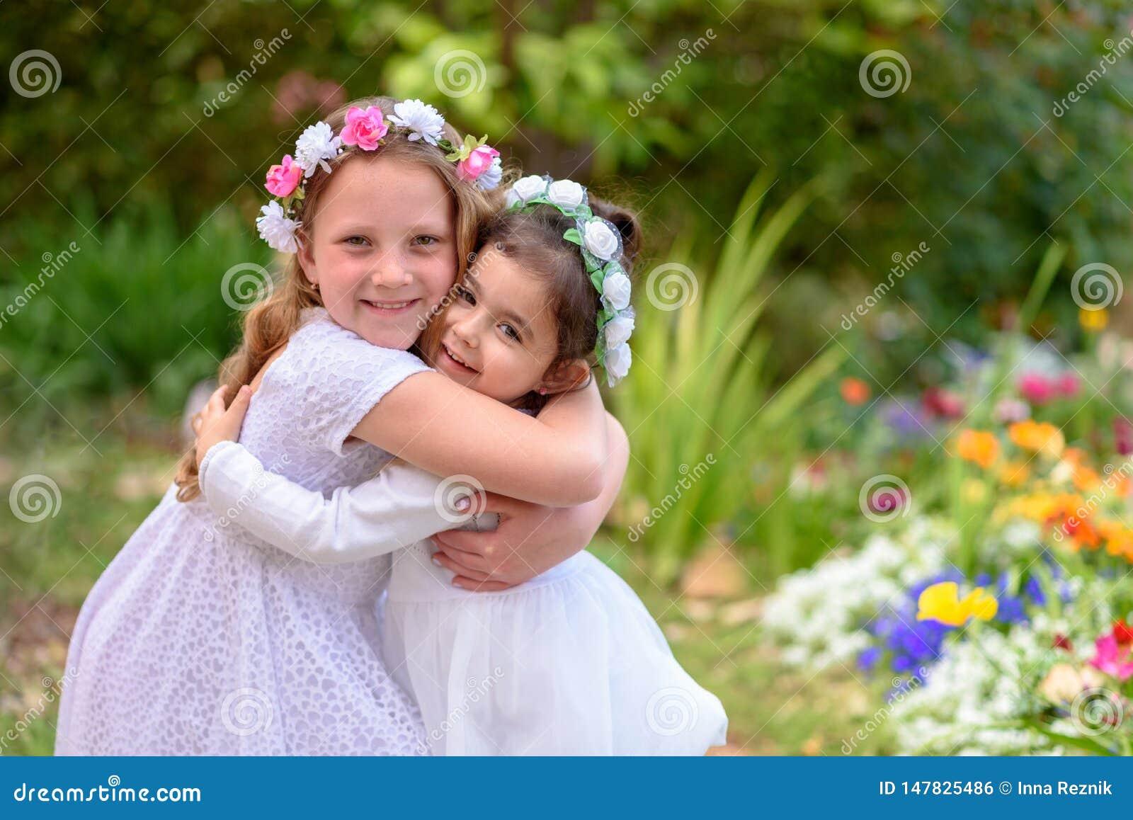 Twee meisjes in witte kleding die pret hebben een de zomertuin