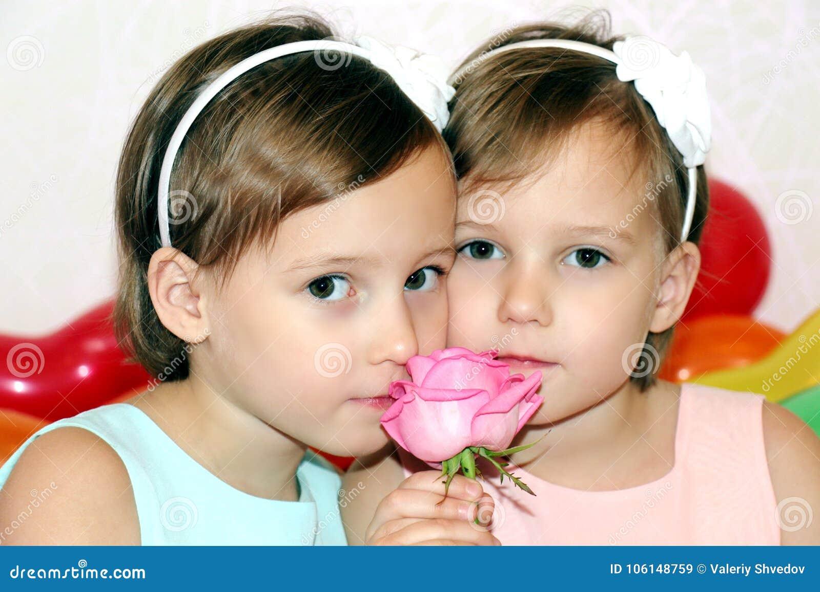 Twee meisjestweelingen in verjaardag met bloem namen op de achtergrond van helder gekleurd ballenclose-up toe