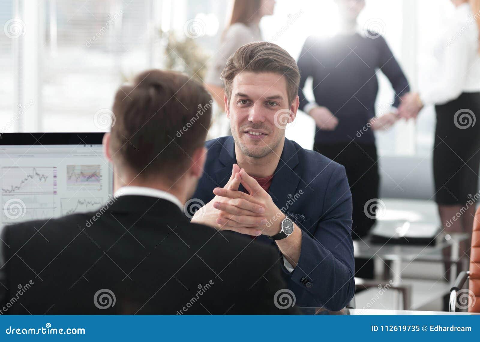 Twee mensen bespreken de groei van het bedrijf, die de het toenemen grafiek op het computerscherm bekijken