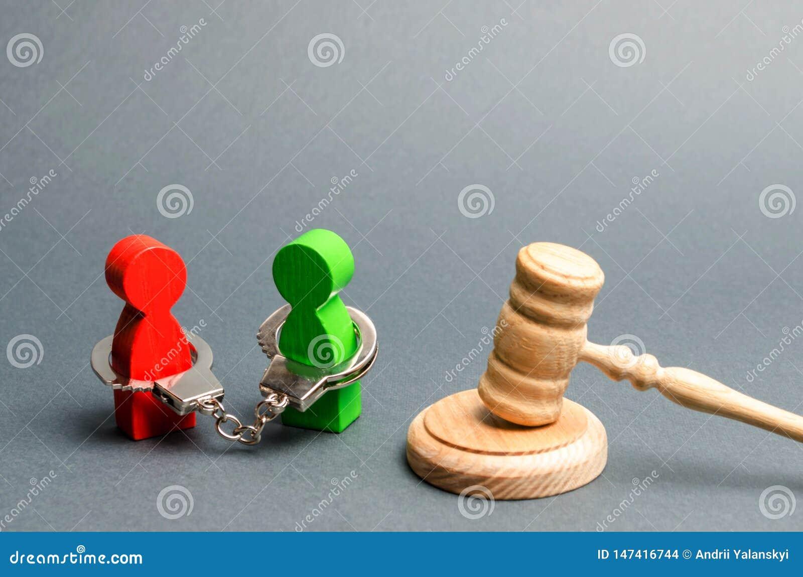 Twee mensen de handboeien om:doen aan elkaar en tribune dichtbij de hamer van de rechter Geschillenbeslechting door hof Bedrijfsc
